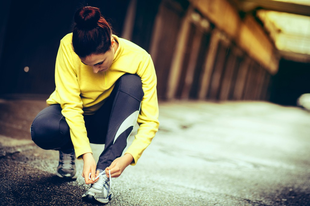 young woman preparing for a run/tied shoelace
